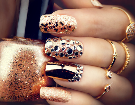 style: Golden holiday style bright manicure with gems and sparkles. Trendy accessories