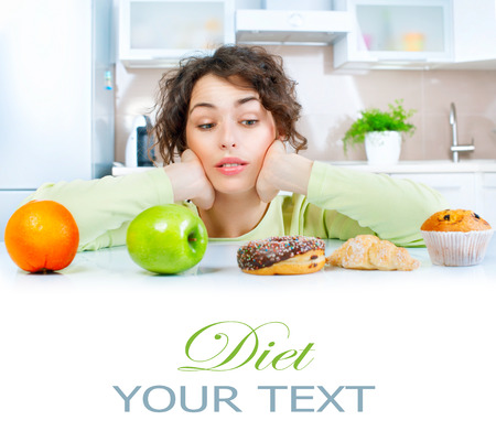 unhealthy diet: Dieting concept. Beautiful young woman choosing between fruits and sweets Stock Photo
