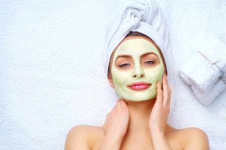 tratamientos corporales: Mujer del balneario que aplica la máscara facial de arcilla Foto de archivo