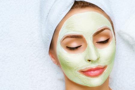 limpieza de cutis: Retrato de la hermosa chica con una toalla en la cabeza que aplica la m�scara facial