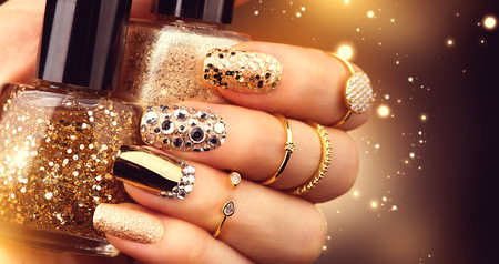 gems: Golden manicure with gems and sparkles. Bottle of nailpolish, trendy accessories
