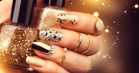 manicure dourado com pedras preciosas e brilhos. Garrafa de nailpolish, acessórios de moda