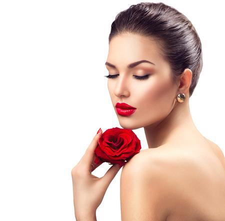 赤いバラの花を持つ美容女性