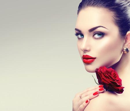 belle brune: mode de beaut� pour le visage femme mod�le. Portrait de rouge, rose, fleur Banque d'images