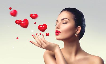 hacer el amor: Mujer de la belleza con maquillaje perfecto hasta que sopla corazones de San Valentín