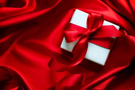 Caja de regalo de San Valentín con la cinta de satén rojo sobre fondo de seda roja Foto de archivo