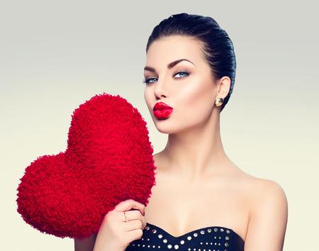 Splendida giovane donna bruna con cuore a forma di cuscino rosso Archivio Fotografico
