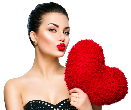 lipstick kiss: Gorgeous young brunette woman with heart shaped red pillow Stock Photo