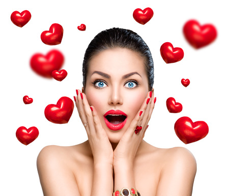 Beauty fashion surprised woman with flying red hearts Archivio Fotografico