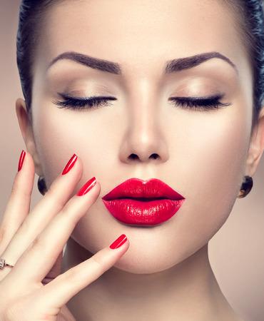 Mooie mode vrouw model gezicht portret met rode lippenstift en rode nagels