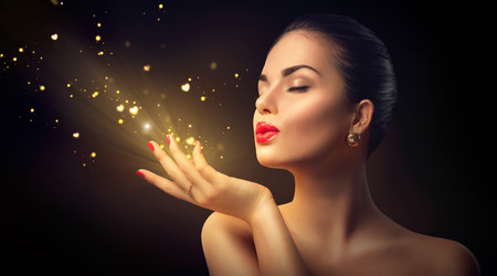 uroda: Piękna młoda kobieta dmuchanie magiczny pył ze złotymi serc Zdjęcie Seryjne