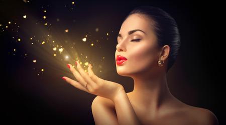 skönhet: Skönhet ung kvinna blåser magiskt damm med gyllene hjärtan Stockfoto