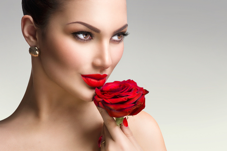 moda: Modelka dziewczyna z czerwoną różą w ręku