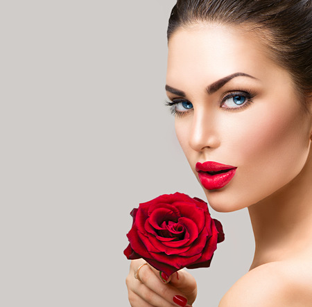 red nail colour: Beauty fashion model woman face. Portrait with red rose flower