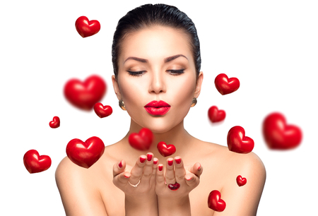 beso labios: Mujer de la belleza con maquillaje perfecto que sopla corazones Valentine Foto de archivo