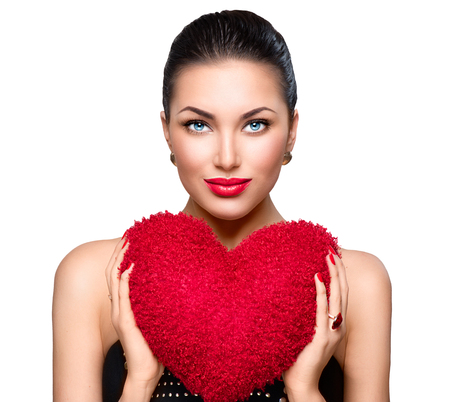 shaped: Gorgeous young brunette woman with heart shaped red pillow Stock Photo