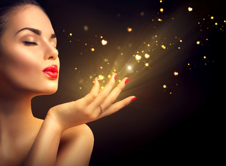 golden background: Beauty young woman blowing magic dust with golden hearts Stock Photo