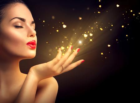 oro: Belleza de la mujer joven que sopla el polvo mágico con corazones de oro