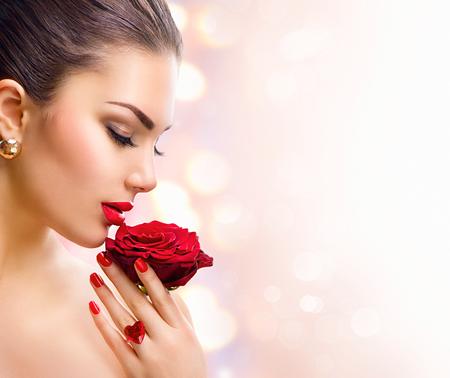 美女: 時裝模特兒女孩的臉肖像與紅玫瑰在她的手
