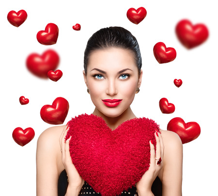 Gorgeous young brunette woman with heart shaped red pillow. Perfect make up. Valentine Day