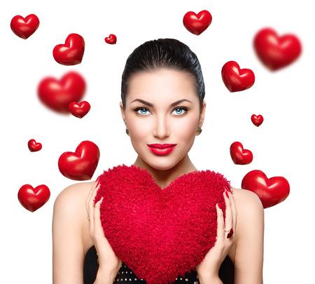 brunette: mujer joven morena preciosa, con forma de corazón rojo almohada. Perfecto maquillaje. Día de San Valentín
