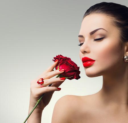 레드 패션 모델 소녀 초상화는 그녀의 손에 장미