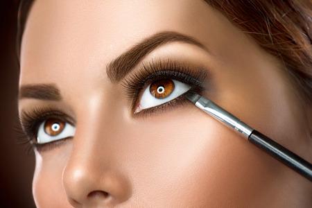 oči: Žena použití make-up detailní. oční linky