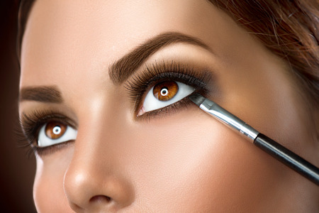 ojos marrones: Mujer de aplicar el maquillaje de cerca. Delineador de ojos Foto de archivo