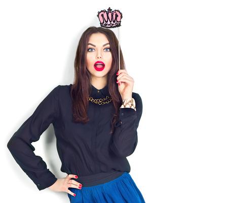 corona reina: Sorprendido modelo de chica atractiva que sostiene la corona divertido en el palillo aislado en blanco