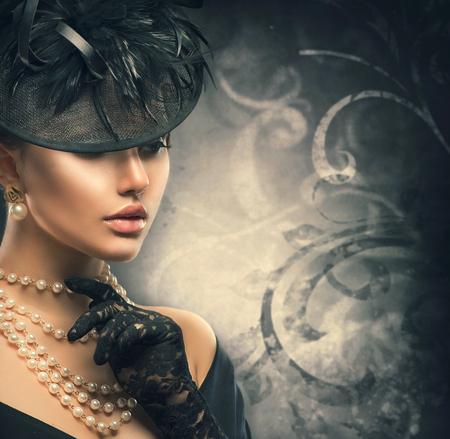 vintage: Retrato retro da mulher. Menina do estilo do vintage que veste o chapéu à moda antiga