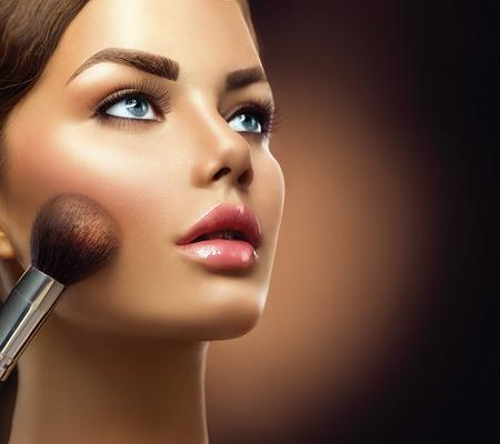 blue face: Makeup. Beauty model girl applying make-up closeup