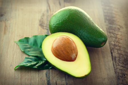 Avocado. Organic avocados with leaves on a wooden table 스톡 콘텐츠