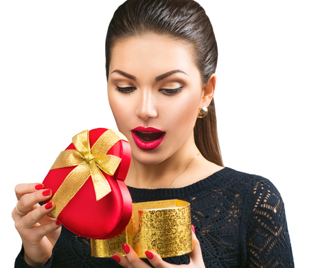 Beautiful surprised young woman opening heart shaped gift box Stock Photo
