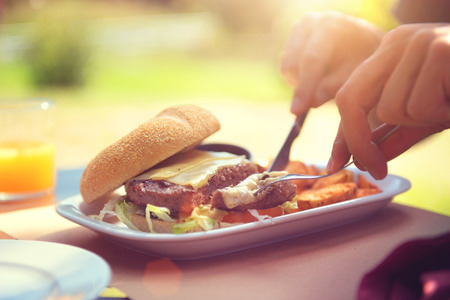 tastes: Man eating burger with fries and orange juice on summer terrace