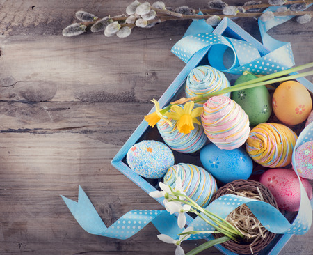 Easter concept. Colorful blue eggs and spring snowdrop flowers over wooden background