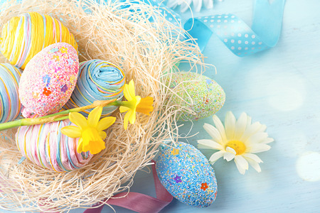 Easter eggs in the nest with spring flowers over wooden background
