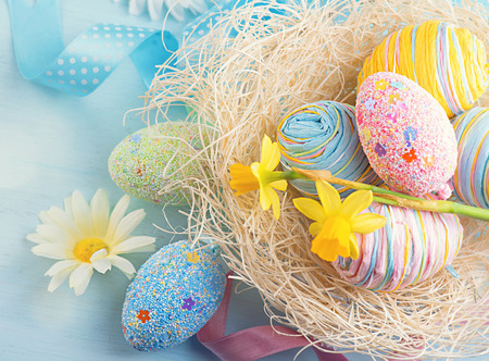Easter eggs in the nest with spring flowers over wooden background Stock Photo