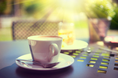 light house: Cup of coffee on the table in sun light