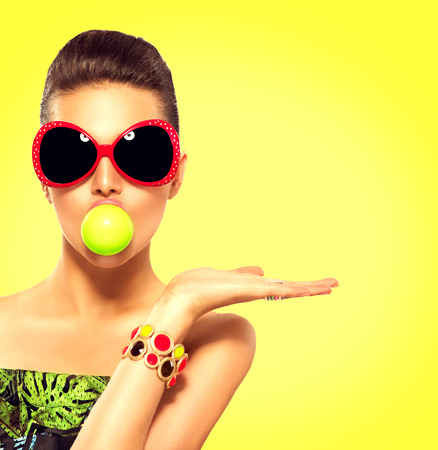 moda: menina modelo de verão usando óculos de sol com bolha verde da goma de mascar