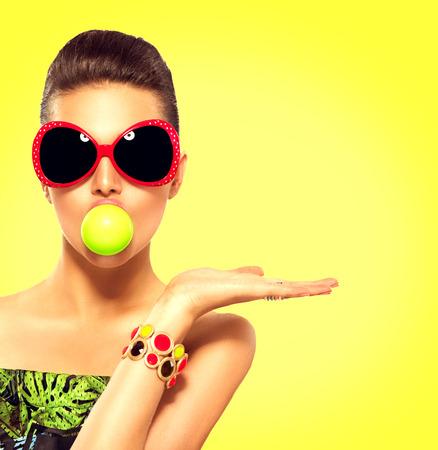 moda: menina modelo de ver�o usando �culos de sol com bolha verde da goma de mascar