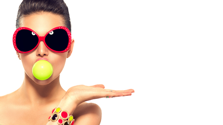 Fashion model girl wearing sunglasses with green bubble of chewing gum Stok Fotoğraf