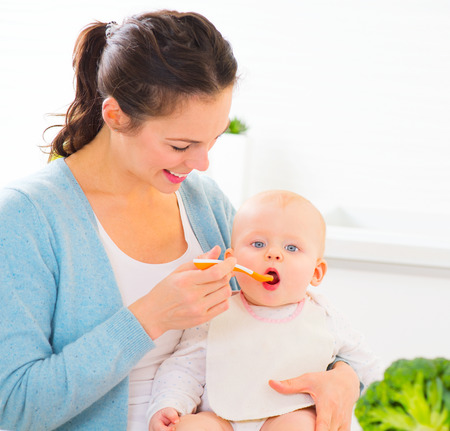 parents and baby: Mother feeding her baby girl with a spoon Stock Photo