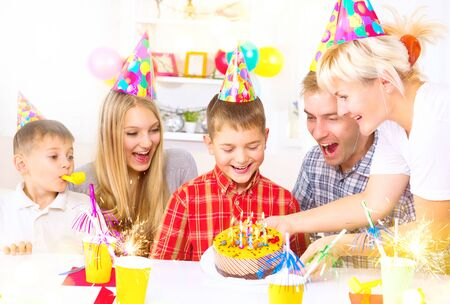 blows: Birthday. Little boy blows out candles on birthday cake