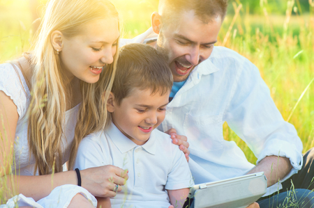 Happy young family with kid using tablet pc in summer park photo
