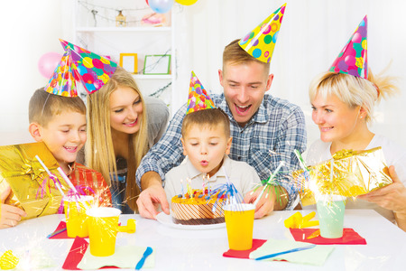Birthday. Little boy blows out candles on birthday cake photo