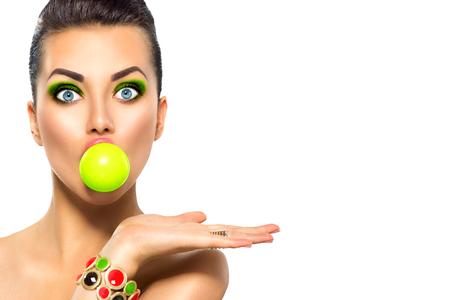 ガムを噛むと明るいメイクの緑のバブルと面白いモデル美少女