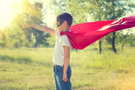 Little boy wearing superhero costume and having fun outdoors