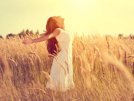 Muchacha de la belleza con el pelo largo disfrutando de la naturaleza, que levanta las manos