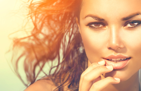 Beauty Sunshine Girl portret. Model vrouw onder de hete zon op het strand Stockfoto