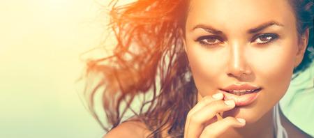 Sol de la belleza retrato chica. Mujer modelo bajo el calor del sol en la playa
